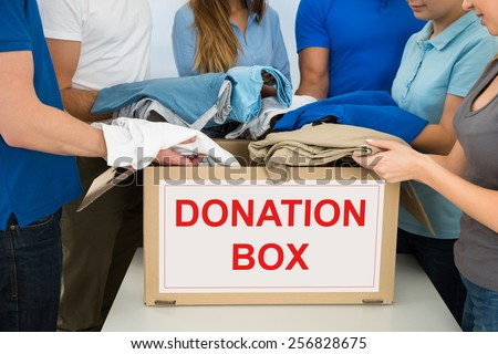 Close-up Of People Putting Clothes Inside Donation Box - stock photo