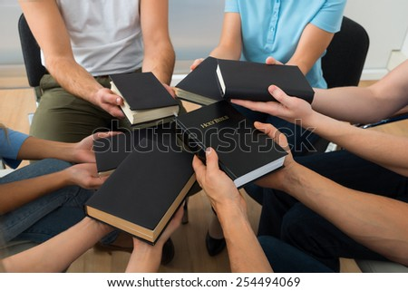 Close-up Of People Sitting Together Holding Holy Bible - stock photo