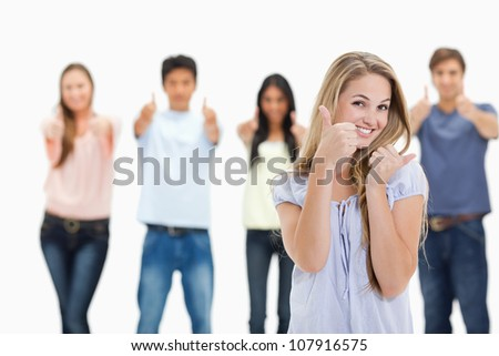 Close-up of people smiling and approving with one young woman in foreground against white background - stock photo