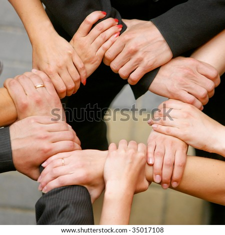 Close up of people that hold hands together - stock photo