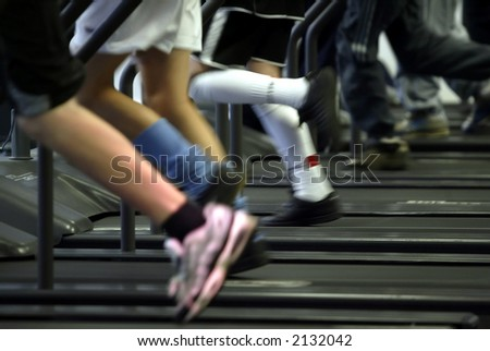 close up of peoples legs running on treadmills with motion blur - stock photo
