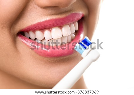 Close up of perfect and healthy teeth with electric toothbrush  - stock photo