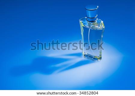 Close up of perfume bottle on blue background - stock photo