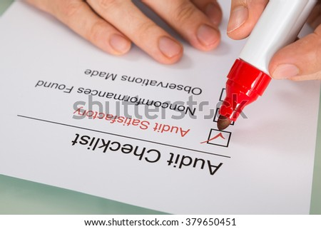 Close-up Of Person Filling Audit Checklist Form - stock photo