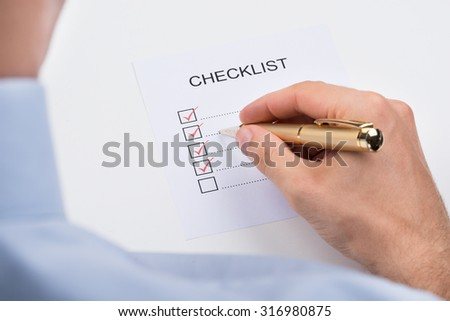 Close-up Of Person Filling Checklist Form With Pen - stock photo