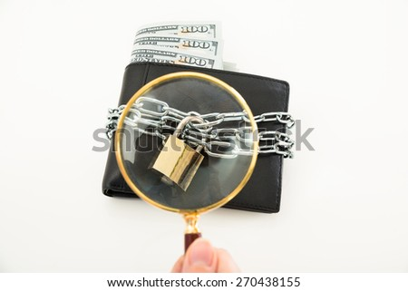 Close-up Of Person Hand Examining Money Wallet With Magnifying Glass - stock photo