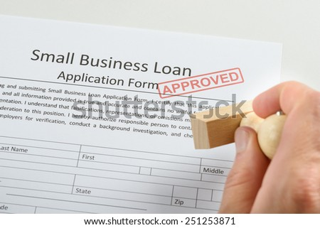 Close-up Of Person Hand Holding Approved Rubber Stamp Over Loan Application Form - stock photo