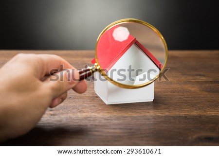 Close-up Of Person Hand Holding Magnifying Glass Over A Miniature House On The Table - stock photo