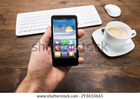 Close-up Of Person Hand Holding Mobile Phone With Apps And Cup Of Tea On Desk - stock photo
