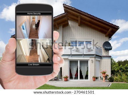Close-up Of Person Hand Holding Mobile Phone With Home Security System - stock photo