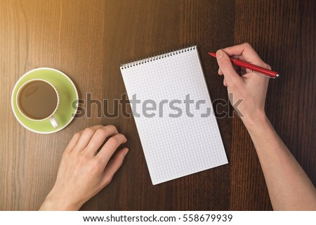 Close-up Of Person Hand Holding Pencil On Blank Notepad Near cup of coffee At Wooden Desk