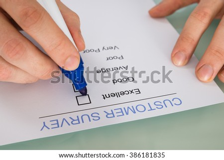 Close-up Of Person Hand Marking On Customer Survey Form With Blue Marker