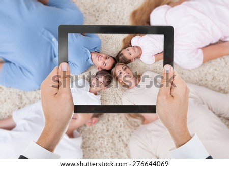 Close-up Of Person Hand Photographing Family Lying On Beach - stock photo