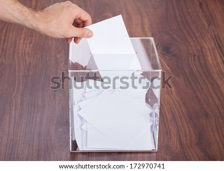 Close-up Of Person Hand's Putting Ballot In Box Kept On Wooden Table - stock photo