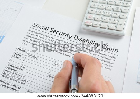 Close Up Of Person Hand With Pen And Calculator Filling Social Security  Disability Claim Form