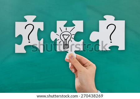 Close-up Of Person Hand With Puzzle Showing Bulb And Question Mark Symbol - stock photo