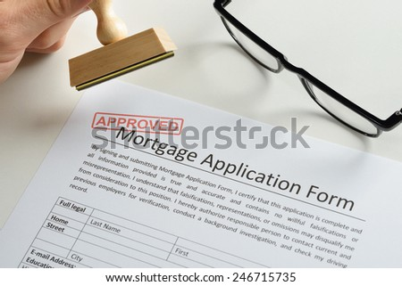 Close-up Of Person Hand With Rubber Stamp And Red Approved Mark On Mortgage Application - stock photo