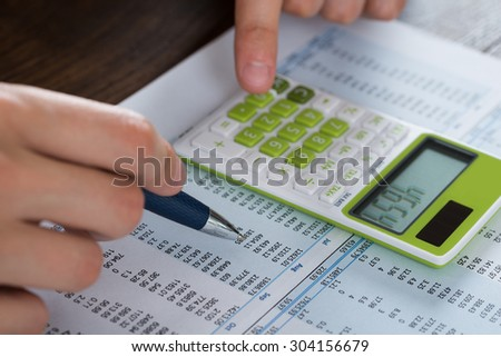Close-up Of Person Hands Analyzing Accounting Document With Calculator - stock photo