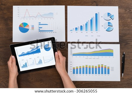 Close-up Of Person Hands Analyzing Financial Charts At Desk - stock photo