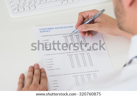 Close-up Of Person Hands Filling Survey Form With Pen