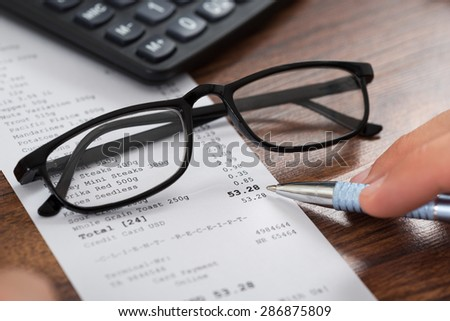 Close-up Of Person Hands Holding Pen Over Shopping Receipt And Eyeglasses - stock photo