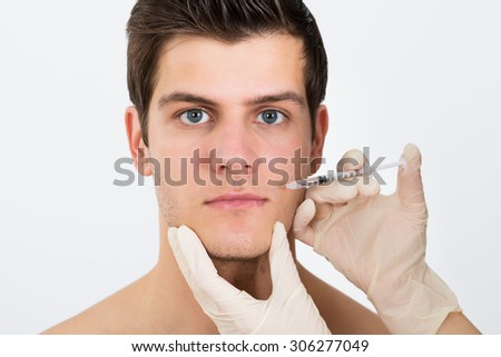 Close-up Of Person Hands Injecting Syringe On Young Man Face - stock photo