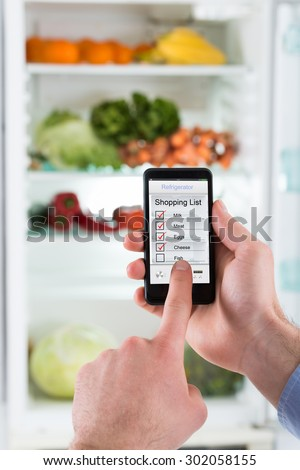 Close-up Of Person Hands Making Shopping List On Mobile Phone Display Connected To Refrigerator - stock photo