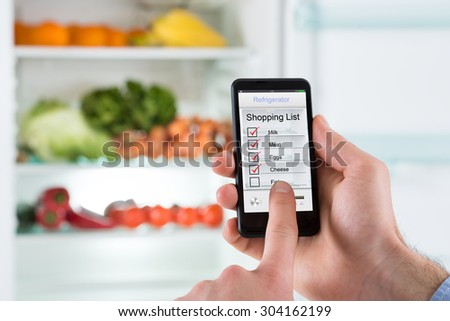 Close-up Of Person Hands Marking Shopping List On Mobile Phone In Front Open Fridge - stock photo