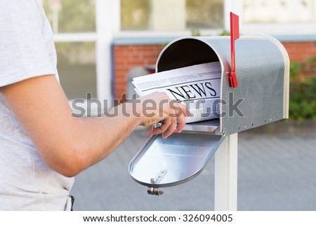 Close-up Of Person Hands Opening His Mailbox To Remove Newspaper - stock photo