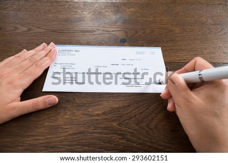 Close-up Of Person Hands Signing Cheque With Pen At Desk - stock photo