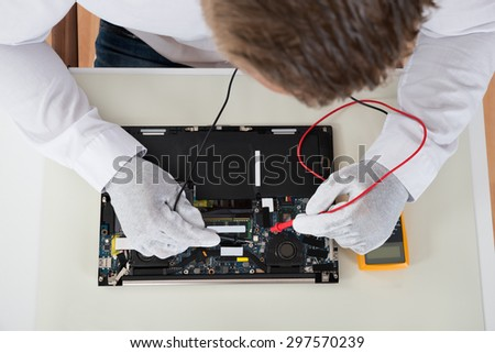 Close-up Of Person Hands Testing Laptop Motherboard Using Multimeter - stock photo