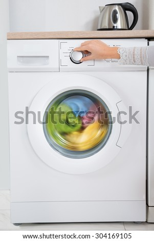 Close-up Of Person Hands Turning Button Of Washing Machine Appliance