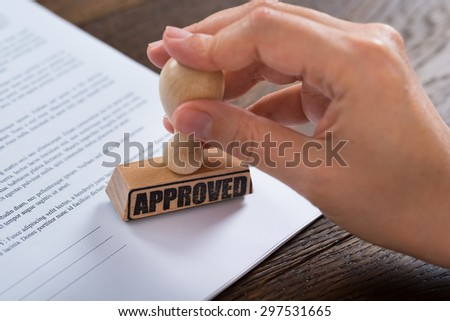 Close-up Of Person Hands Using Stamper On Document With The Text Approved - stock photo