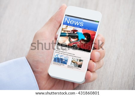 Close-up Of Person Hands With Mobile Phone Showing News Over Wooden Desk - stock photo