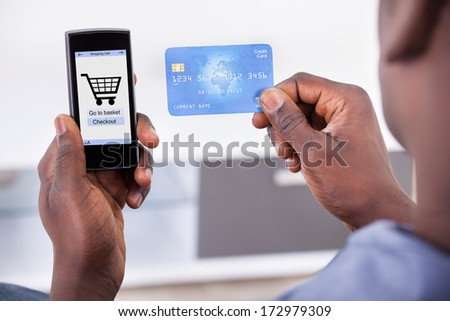 Close-up Of Person Holding Credit Card With Mobile Phone Showing Shopping Cart Symbol - stock photo