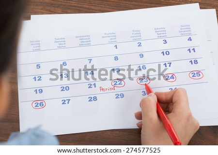 Close-up Of Person Marking Menses Date On Calendar - stock photo