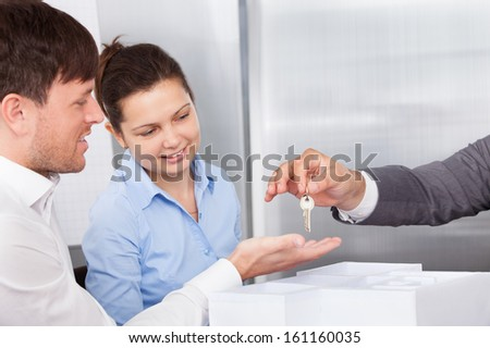 Close-up Of Person's Hand Giving Keys To A Young Man - stock photo
