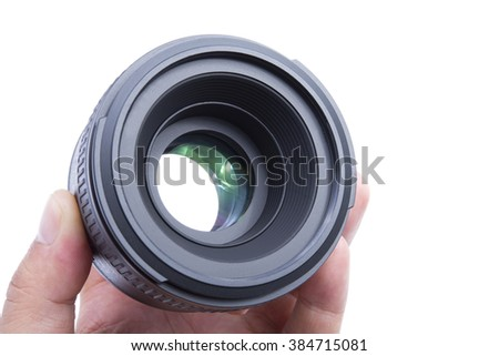 Close-up of person's hand holding camera lens over white background. - stock photo