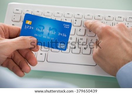 Close-up Of Person's Hand Holding Car While Using Keyboard - stock photo