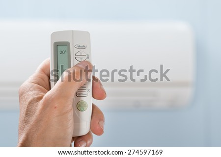 Close-up Of Person's Hand Holding Remote In Front Of Air Conditioner