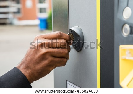 Close-up Of Person's Hand Inserting Coin Into Parking Meter