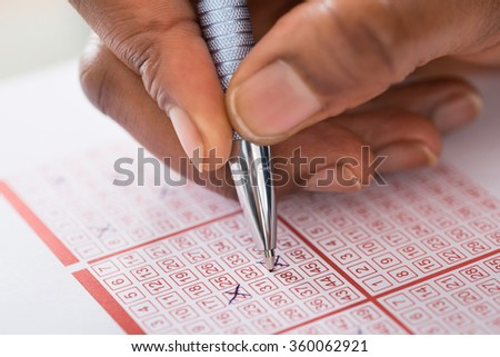 Close-up Of Person's Hand Marking Number On Lottery Ticket With Pen - stock photo