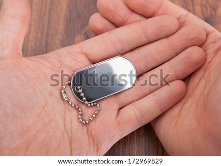 Close-up Of Person's Hand On Wooden Table Holding Dog Tag - stock photo