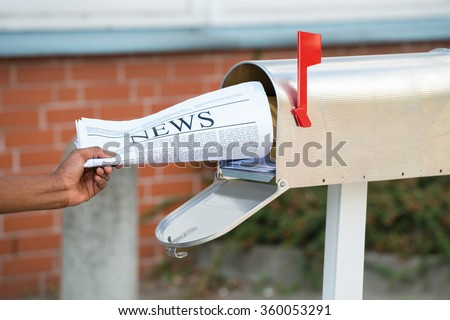 Close-up Of Person's Hand Opening Mailbox To Remove Newspaper - stock photo
