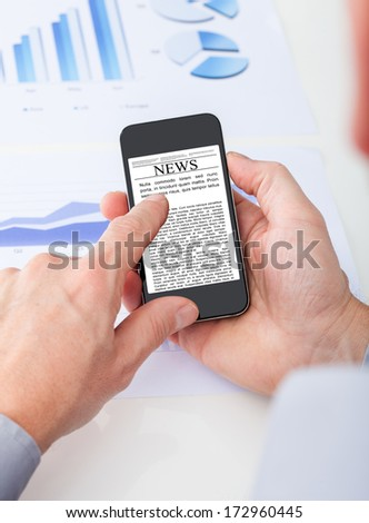 Close-up Of Person's Hand Reading News On Cell Phone - stock photo