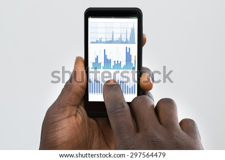 Close-up Of Person's Hand Using Cellphone With Graph On Screen - stock photo