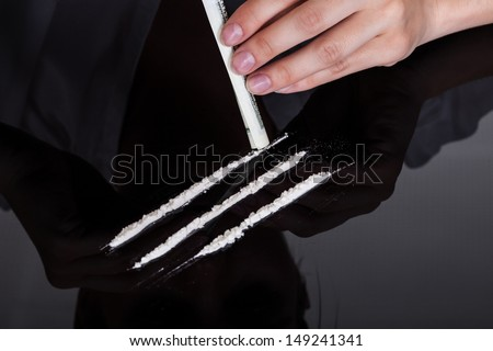 Close-up Of Person Sniffing Cocaine Drugs With Rolled Bank Note - stock photo