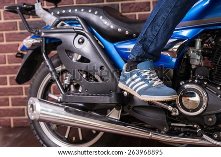 Close Up of Person Wearing Blue Running Shoe Standing on Foot Pegs of Blue Cruiser Style Motorcycle Indoors in front of Brick Wall