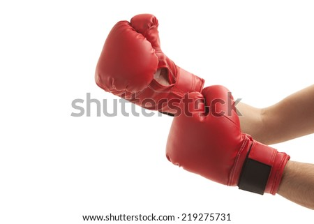 Close-up of person wearing boxing gloves over white background