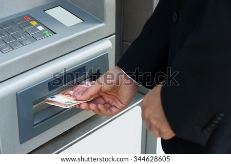 Close-up Of Person Withdrawing Money From Atm Machine - stock photo
